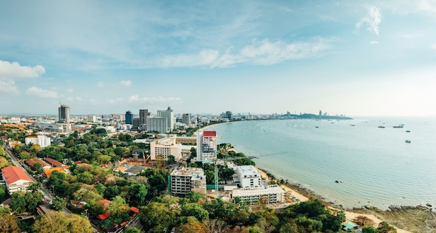 Panorama of cityscape with buildings and seascape with bright sky and cloud of pattaya beach in chon buri, thailand.