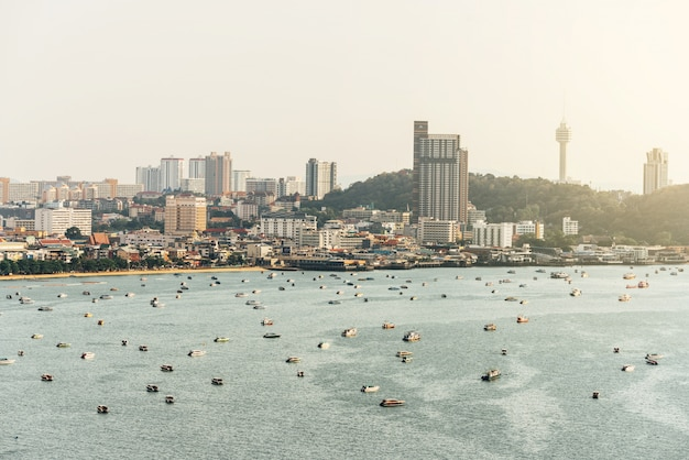 Panorama of cityscape with construction buildings and seascape with boats, bright sky and cloud of pattaya beach, thailand