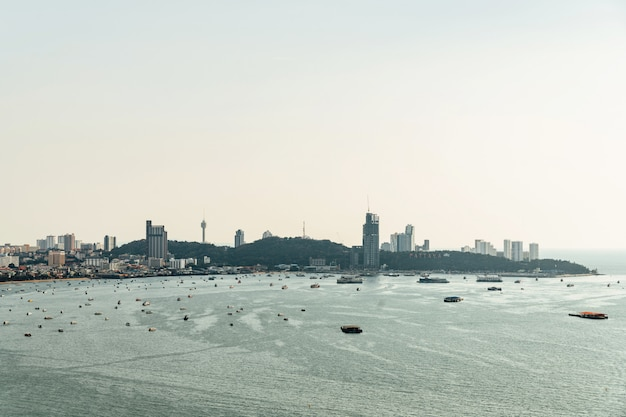 Panorama of cityscape with construction buildings and seascape with boats, bright sky of pattaya beach.