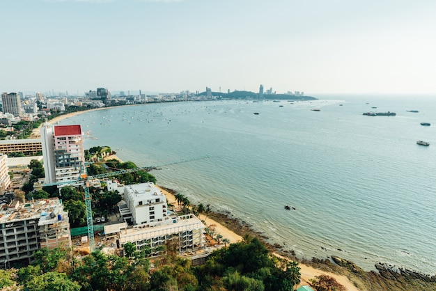 Panorama of cityscape with construction buildings and seascape with bright sky and cloud of pattaya beach.