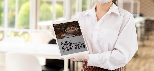 パノラマフェイスマスクとフェイスシールドのウェイトレスをクローズアップ顧客がオンライン非接触メニューをスキャンするためのqrコード付きデジタルタブレットを保持非接触型と新しい通常のレストランの技術コンセプト