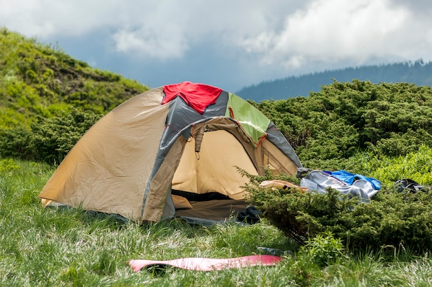 Panorama of cold foggy summer morning and tourist hikers tent in carpathian mountains