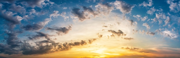Panorama of dramatic sky with clouds at yellow-orange sunset