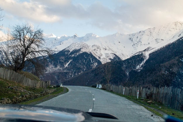 Panorama from the car wind window of georgian mountains and snow