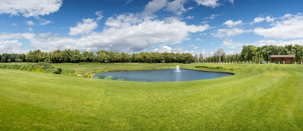 Panorama of golf course with pond in sunny summer day