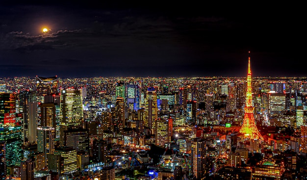 Panorama of the modern city with lighting of architecture building under night skyline and light full moon and cloud in tokyo city, japan.