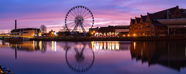 Panorama of motlawa river and ferris wheel with water reflection in old town of gdansk at night