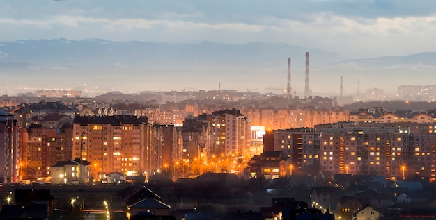 Panorama of night aerial view of ivano-frankivsk city, ukraine. scene of modern night city with bright lights of tall buildings. residential quaters and construction cranes in modern urban space.