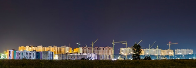 Panorama night view of many building cranes at construction site of new modern residential area
