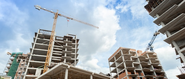 푸른 하늘 배경에 건설 중인 다층 주거용 건물과 크레인의 파노라마