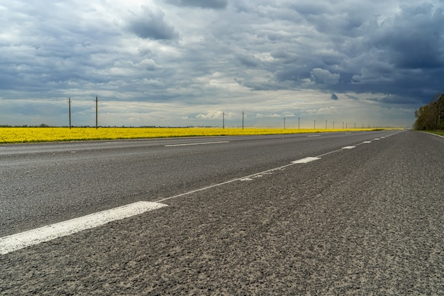 暗い雨の雲が付いている道のパノラマ