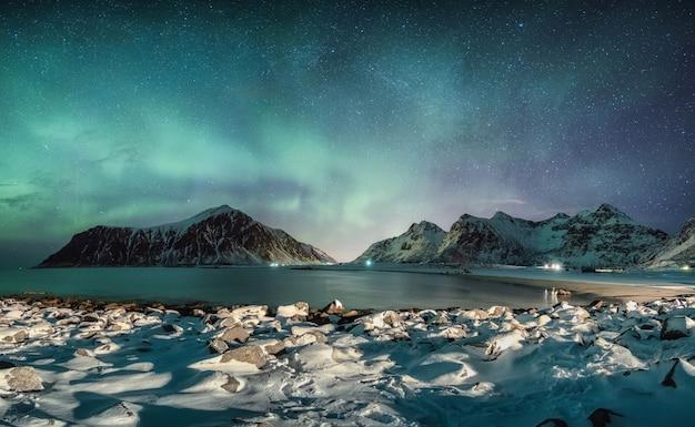 ロフォーテン諸島、スカグサンデンビーチの雪に覆われた海岸線と山脈の上の星とオーロラのパノラマ