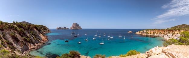 Панорама красивой бухты кала хорт с морскими парусными яхтами и горы эс ведра. ибица, балеарские острова. испания