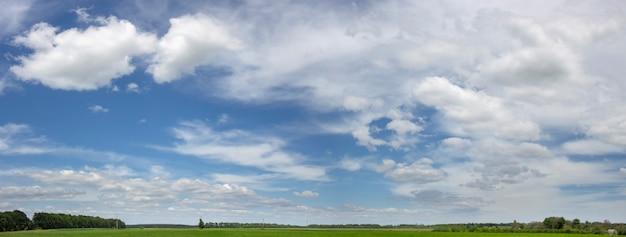 晴れた日に作物と農地の上の青い曇り空のパノラマ。