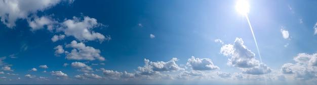 Панорама голубого неба с облаками и солнцем