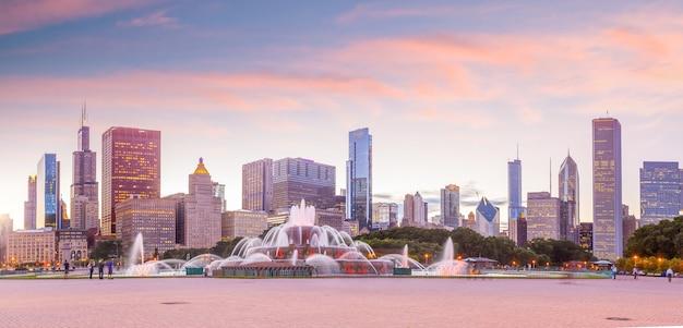 高層ビルと日没時のバッキンガム噴水とシカゴのスカイラインのパノラマ
