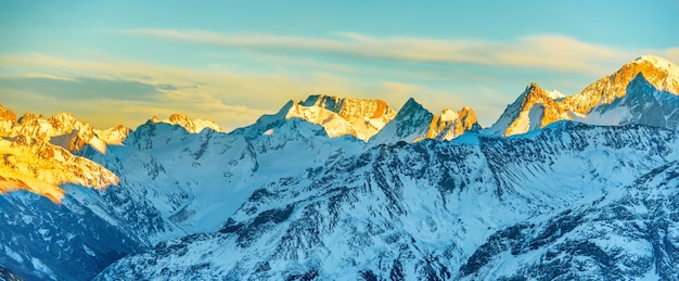 高山のパノラマは日没時にピークに達します。雪の丘の風景
