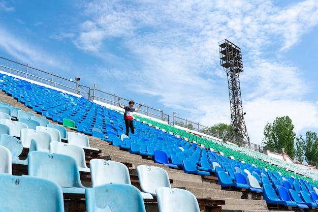 Панорама огромных зрительских мест стадиона с мужчиной, смотрящим на концерты музыкального мероприятия