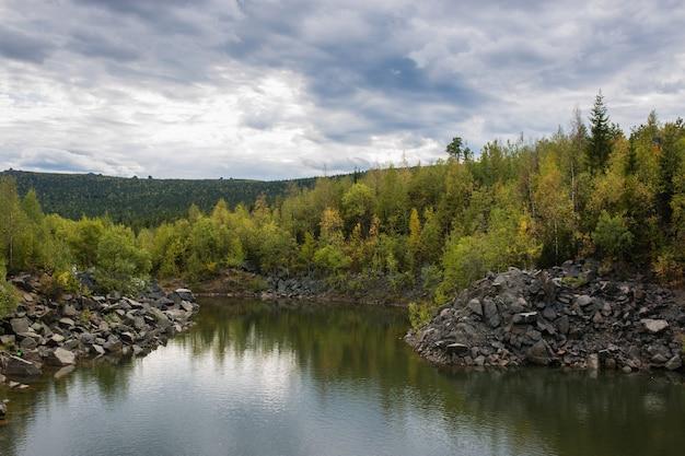 Панорама озерных сцен в национальном парке качканар, россия, европа. пасмурная погода, драматическое голубое небо, вдалеке зеленые деревья. красочный летний день