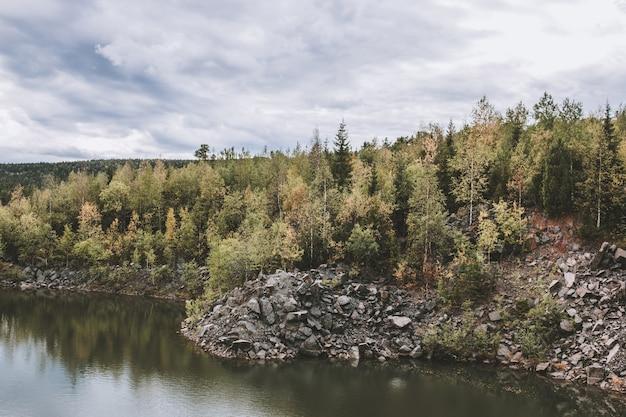 국립 공원 kachkanar, 러시아, 유럽에서 호수 장면의 파노라마. 흐린 날씨, 극적인 푸른 하늘, 멀리 푸른 나무. 다채로운 여름날