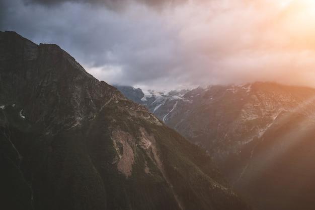 Панорама сцены туманных гор с драматическим голубым небом в национальном парке домбая, кавказ, россия. летний пейзаж и солнечный день