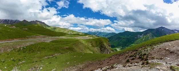 산과 산길, 야생 풍경과 푸른 하늘의 파노라마. 군사 조지아 도로