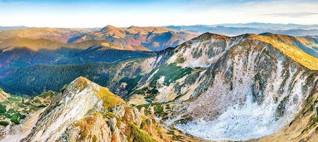 日没時の山々のパノラマ。雪と黄色い草のある山と丘