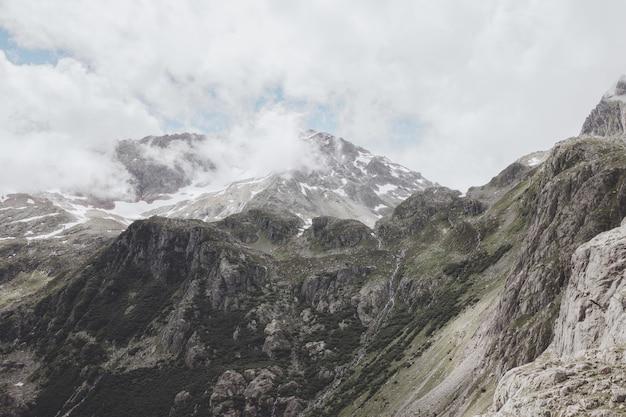 Панорама гор на маршруте моста trift в национальном парке швейцарии, европе. летний пейзаж, солнечная погода, драматическое облачное небо и солнечный день