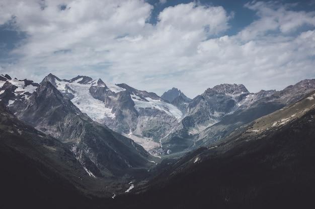 러시아 코카서스 돔베이 국립공원에서 극적인 푸른 하늘이 있는 산의 파노라마. 여름 풍경과 화창한 날