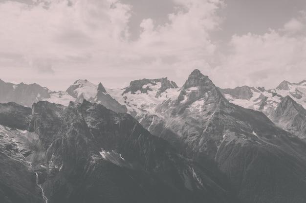 Панорама гор с драматическим голубым небом в национальном парке домбай, кавказ, россия. летний пейзаж и солнечный день