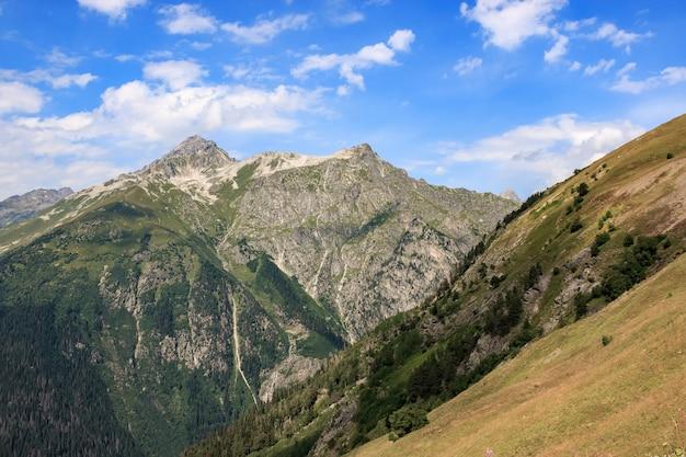 ロシア、コーカサス、ドンベイの国立公園の劇的な青い空と山のシーンのパノラマ。夏の風景と晴れた日