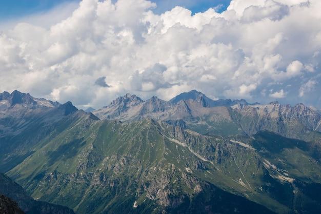 ロシア、コーカサス、ドンベイの国立公園の劇的な曇り空と山のシーンのパノラマ。夏の風景と晴れた日