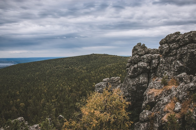 Панорама гор в национальном парке качканар, россия, европа. пасмурная погода, драматическое голубое небо, вдалеке зеленые деревья. красочный летний день