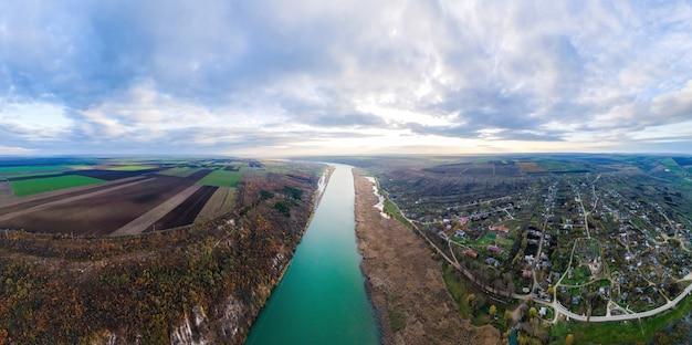 モルドバの自然のパノラマ。川のほとりに村があり、地平線に広がる畑のあるドニエストル川。ドローンからの眺め