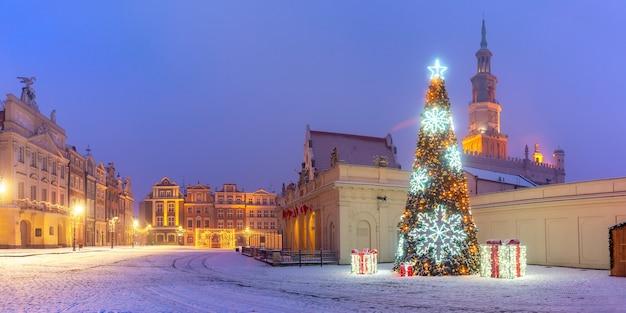 雪の降る夜、ポズナンの旧市街の旧市場広場にあるポズナン市庁舎とクリスマスツリーのパノラマ