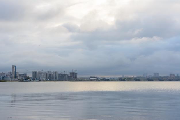 カザン川を渡ったカザン市の住宅中心地区のパノラマ。カザン、タタールスタン、ロシア。キャプション:「武道宮殿アクバーズ」。