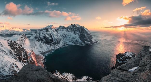 ロフォーテン諸島の冬のリテン山とクヴァルビカビーチに沈む夕日のパノラマ