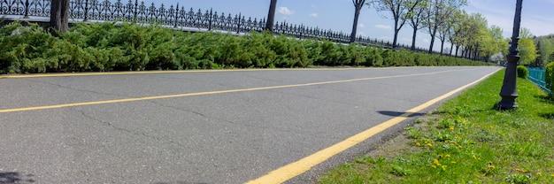 Панорама асфальтированной дорожки через парк в солнечный летний день, по которой бегают спортсмены и катаются велосипедисты