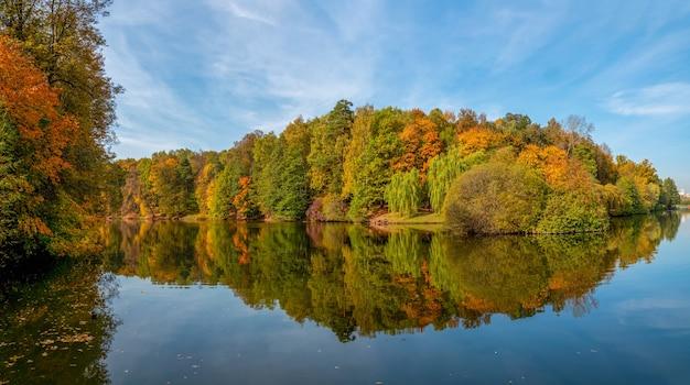 秋の公園のパノラマ。湖のほとりに赤い木々と美しい秋の風景。ツァリツィノ、モスクワ。ロシア。