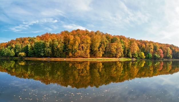 秋の公園のパノラマ。湖のほとりに赤い木々のある美しい秋の風景。ツァリツィノ、モスクワ。
