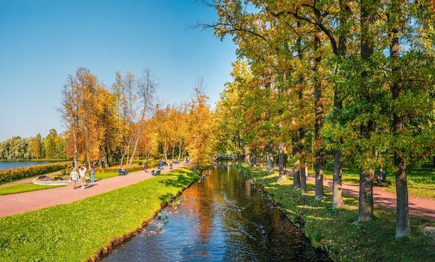 歩く人々のシルエットと秋の公園のパノラマガッチナロシア