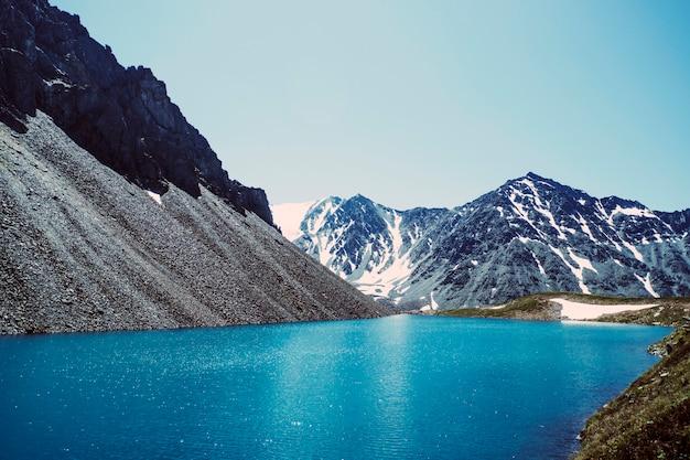 저녁에 산에 있는 아름다운 푸른 호수의 파노라마. 호수의 바닥은 태양 광선 아래에서 잘 빛납니다. 수정 같이 맑은 물에 있는 돌.