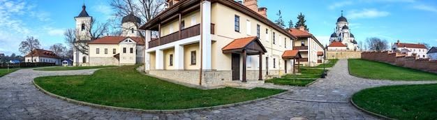 カプリアーナ修道院のパノラマ。目に見える冬と石の教会。裸の木、緑の芝生と建物、モルドバの天気の良い日
