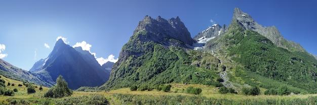 Панорама кавказских гор со скалистыми вершинами и зеленым лесом