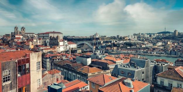 晴れた春の日、赤瓦の屋根とポルトポルトガルのドンルイス橋のある歴史的中心部のパノラマ