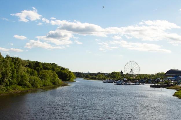 広い川の堤防、青い空、白い雲、背景の観覧車からの風景のパノラマ。ヤロスラヴリ、ロシア、市内中心部
