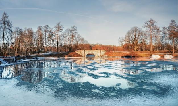 ガッチナの春のロシアの公園のパノラマ。カーピン池は水たまりと氷で覆われています。