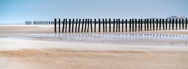 フランスのビーチにある未完成の木製ドックの砂の中の垂直の木板のパノラマ