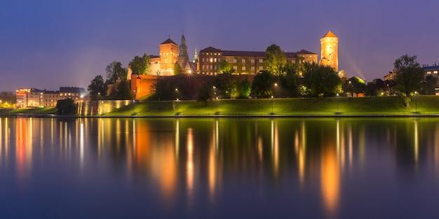 ポーランド、クラクフのヴィスワ川から見た夜の川の反射を伴うヴァヴェルヒルのヴァヴェル城のパノラマ