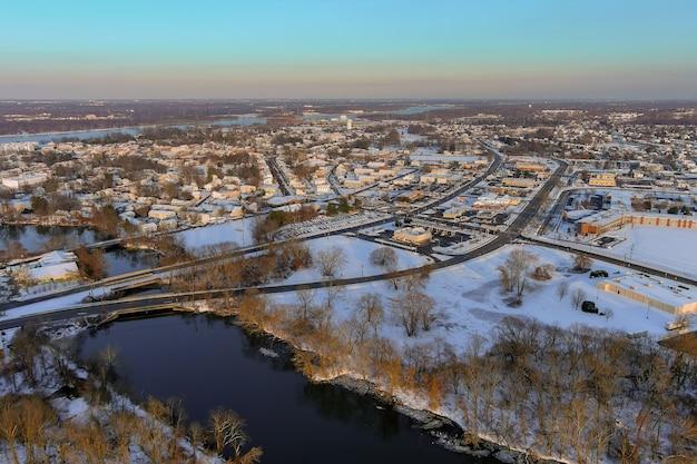 デラウェア川沿いのニュージャージー州バーリントン市の雪に覆われた近隣地区の住宅地のある冬の風景のパノラマ